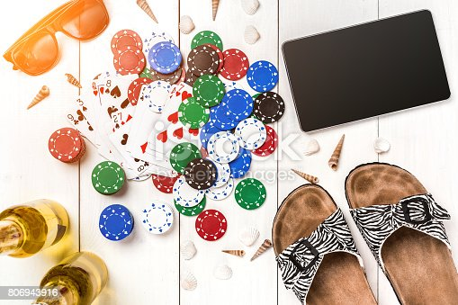 istock Gambling. Poker chips, cards and the dice nearby tablet on wooden table. Top view. Copyspace. Poker 806943916