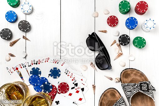 istock Gambling. Poker chips, cards, sunglasses and flip-flops on wooden table. Top view. Copyspace. Poker 1094965320