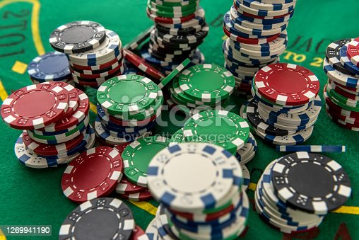 Gambling poker chips on green play field for luck game. Poker chance or risk