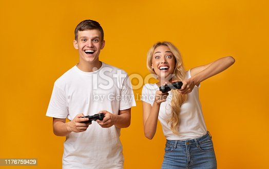 istock Gambling young couple playing video game with joysticks 1176759429
