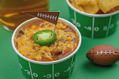 superbowl chili, beer, and party snacks closeup on green field background