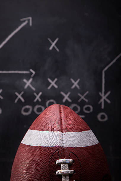Game Day Plan An American football with a play drawn up on a chalkboard in the background.. line of scrimmage stock pictures, royalty-free photos & images