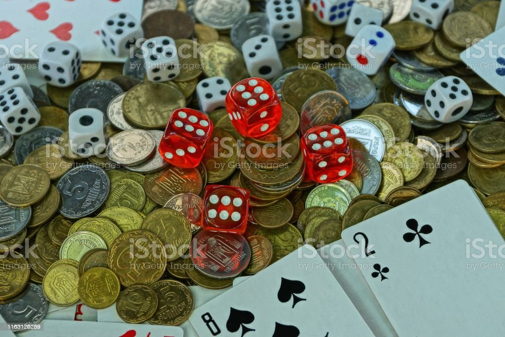 game dice with game cards in a pile with small coins on the table