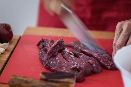 Piece of game meat cut into thin slices using sharp knife, close-up, motion blur on hand and knife