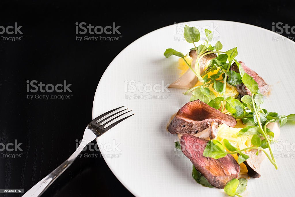 Game meat with herbs on white plate stock photo