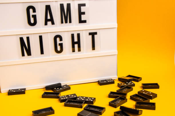 Game night text on lightbox with black dominoes on yellow background, table game stock photo