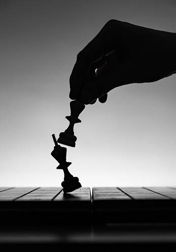 Game of chess. Board with chess pieces silhouettes on white background. Concept of business ideas and competition and strategy ideas. Black and White classic art photo. Weak king was defeated