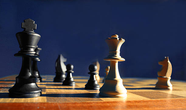 Game of chess someone has checkmated Side lit shot of a chess game adversarial stock pictures, royalty-free photos & images