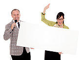 An old fashioned game show host holding a microphone standing with the contestant. Photographed in studio with a purpose built set and props.