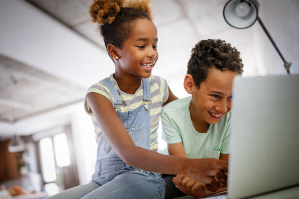 Game, study, fun concept. Happy children spending time with notebook and modern technology. stock photo