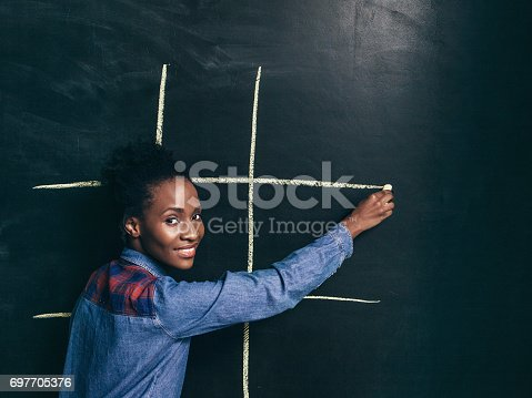 1003539592istockphoto Game tic tac toe, afroamerican girl happy to play 697705376