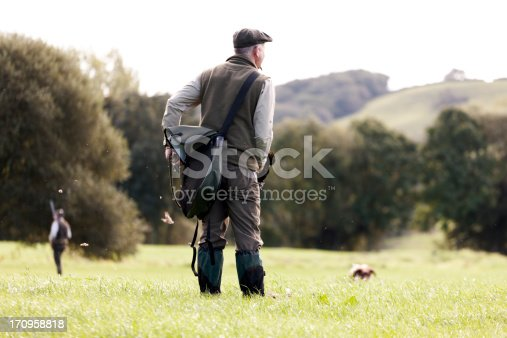 A Gamekeeper watching his dog, a second hunter to the left of the scene, Devon, UK