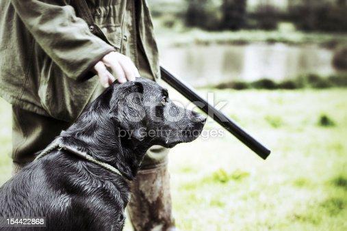 A Gamekeeper standing with his Black Labrador, Devon, UK