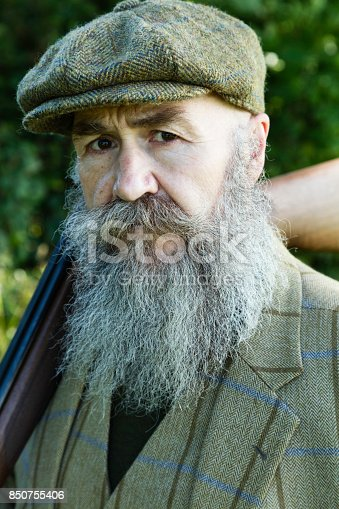 A bearded gamekeeper wearing a three piece suit and cap and carrying a shotgun.