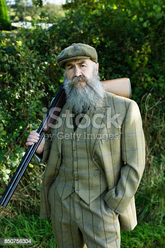 A bearded gamekeeper wearing a three piece tweed suit and with his shotgun.
