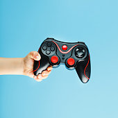 istock A gamepad on a blue background holds a child's hand as a weapon. Minimalistic creative concept of the younger generation of gamers. 1216945130