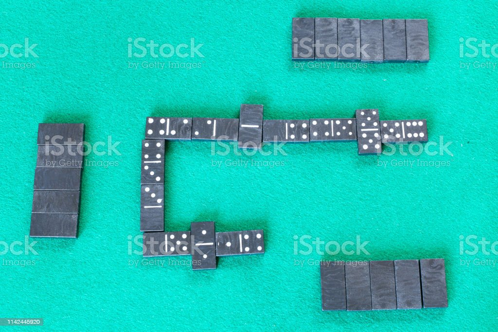 top view of gameplay of dominoes board game with black tiles on green...