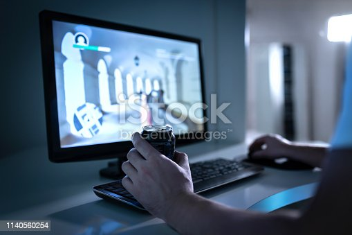 istock Gamer guy playing video game and drinking soda or energy drink from can. Fps videogame in computer monitor. Addicted gaming late at night. Man with addiction to online first person shooters. 1140560254