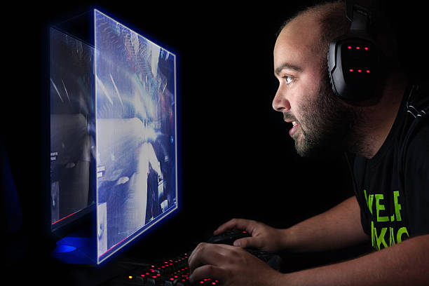 Gamer playing first person shooter game on high end pc stock photo