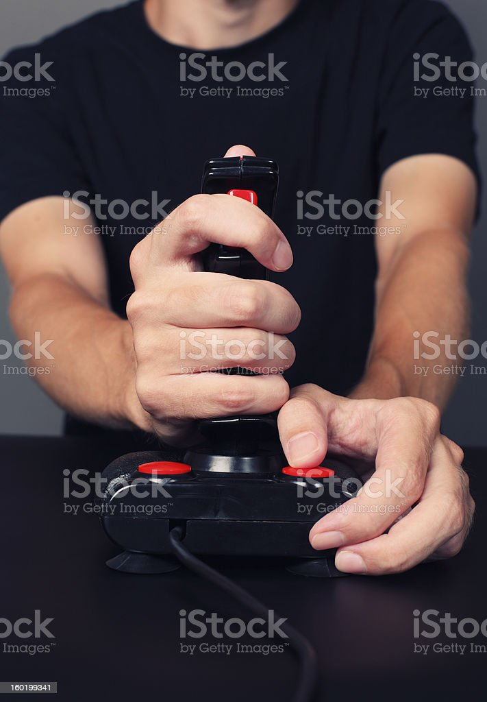 Gamer playing video game with retro joystick stock photo