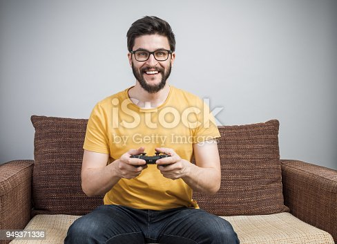 Handsome young man with facial hairs and eyeglasses holding controller and playing video games. Cheerful dude on sofa having fun with internet friends