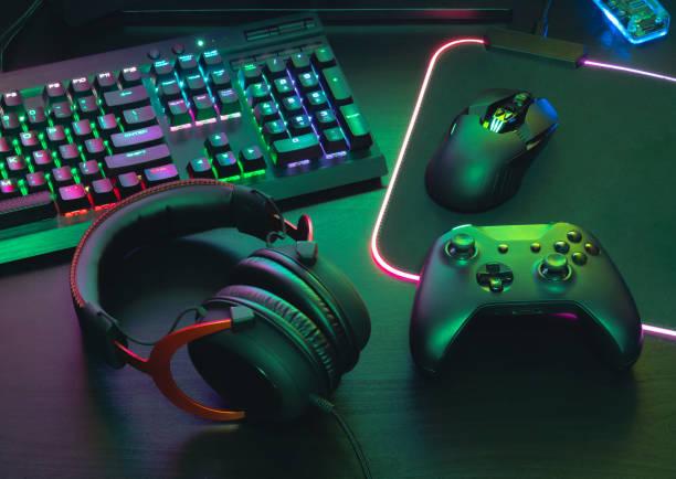gamerwerkruimte concept, bovenaanzicht een gaming-gear, muis, toetsenbord, joystick, headset, mobiele joystick, in ear hoofdtelefoon en muismat op zwarte tafel achtergrond. - vrijetijdsspel stockfoto's en -beelden