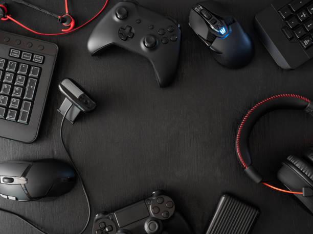 gamer workspace concept, top view een gaming gear, muis, toetsenbord, joystick, headset, mobiele joystick, in ear hoofdtelefoon en muismat op zwarte tafel achtergrond. - gaming stockfoto's en -beelden