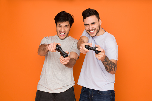 Gamers. Two mates playing video games, orange background