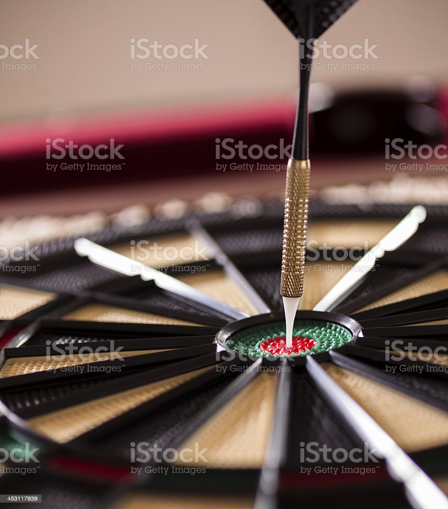 Games: Bullseye. Dart in center of dartboard. Billiards table background. royalty-free stock photo