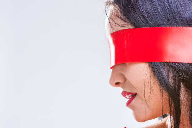 BDSM Games Ideas and Concepts. Caucasian Brunette Woman Posing with Red Ribbon Blinder on Eyes with Passionate Sensual Expression.Horizontal Image Composition