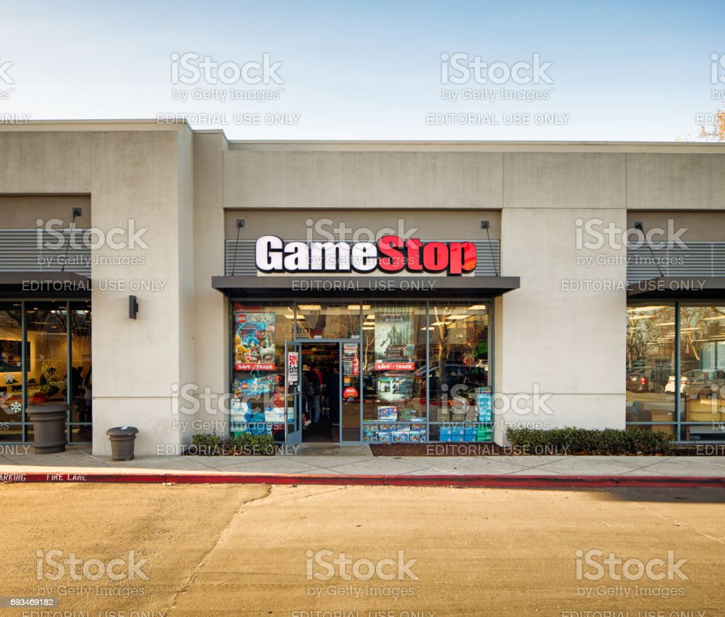 Gamestop video games store entrance facade in strip mall with sign,...