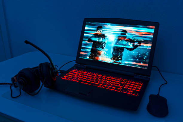 gaming laptop with connected mouse and headphones - esports stock photos and pictures