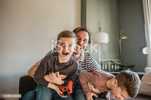 Father is playing video games with his sons