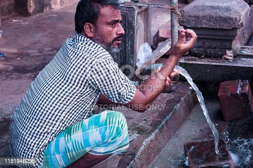 Gandhinagar, Gujrat, India May 2018 - Closeup photo of man washing hands with water from pipe near street road.