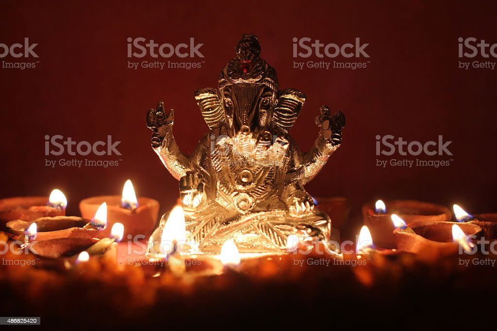 Ganesh idol surrounding with oil lamp, festival season stock photo