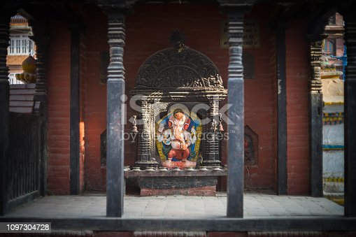 Sunlight obliquely strikes the elephant head of the god Ganesh in a covered shrine