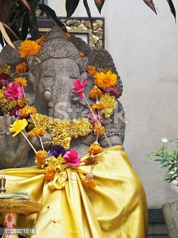 Vertical closeup photo of a beautiful old carved sculpture of the Hindu elephant God, Ganesha, decorated with colourful flower garlands around his neck and a bright shiny golden cloth tied around his lower half. Part of a small offerings tray can be seen in front of the statue which sits in front of a grey cement wall