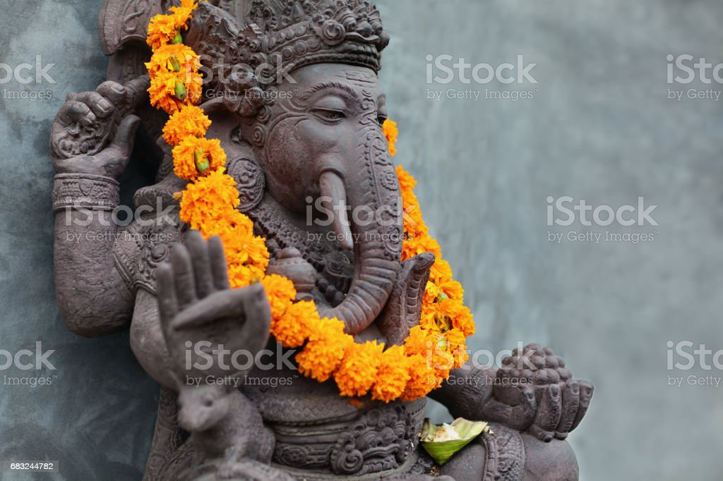 Ganesha with balinese Barong masks, flowers necklace and ceremonial offering stock photo
