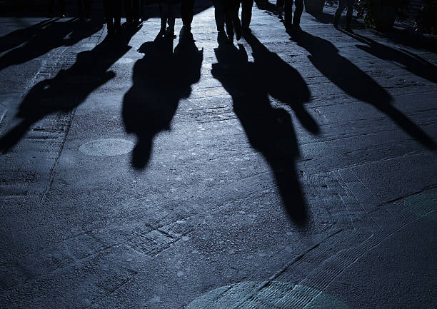 Gang of people advancing on viewer night shadows Concept: group of people advancing on viewer creepy stalker stock pictures, royalty-free photos & images