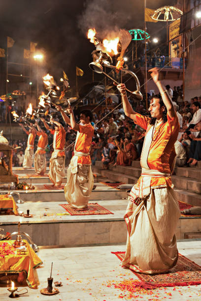 Ganga Aarti ritual VARANASI, INDIA - APRIL 11: An unidentified Hindu priest performs religious Ganga Aarti ritual (fire puja) at Dashashwamedh Ghat on April 11, 2012 in Varanasi, Uttar Pradesh, India dashashwamedh ghat stock pictures, royalty-free photos & images