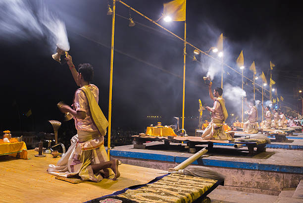 Ganga Aarti, Varanasi, India Varanasi, India - July 03, 2014: Hindu priests wearing traditional clothes conducts religious Ganga Aarti ritual at Dashashwamedh Ghat, Varanasi, India. dashashwamedh ghat stock pictures, royalty-free photos & images