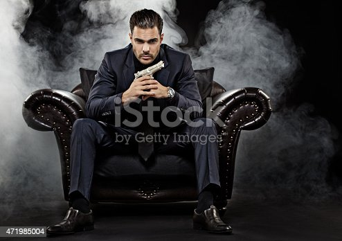 471947536 istock photo gangster holding gun sitting on chair 471985004