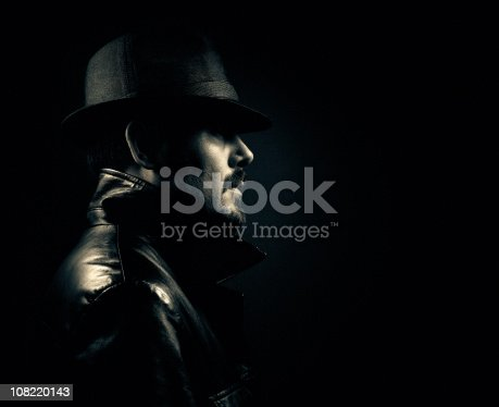 a gangster from the 70s wearing a black leather jacket and hat