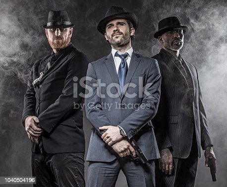 Italian Gangster Mafia Don and bodyguards together in smoky studio shoot