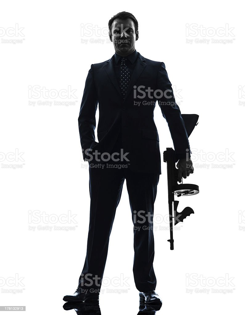 gangster man holding thompson machine gun silhouette royalty-free stock photo
