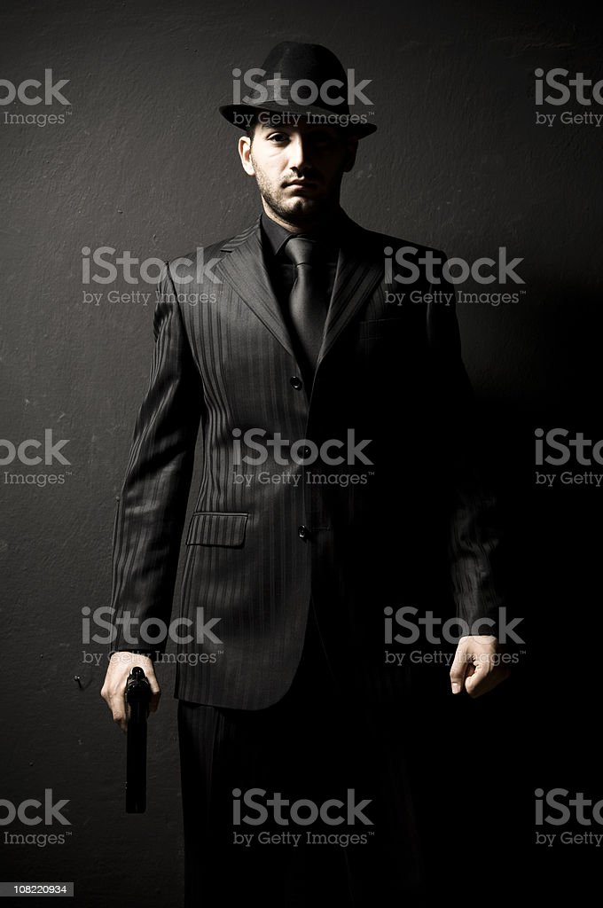 Gangster Man In Black Suit and Hat Holding Gun stock photo