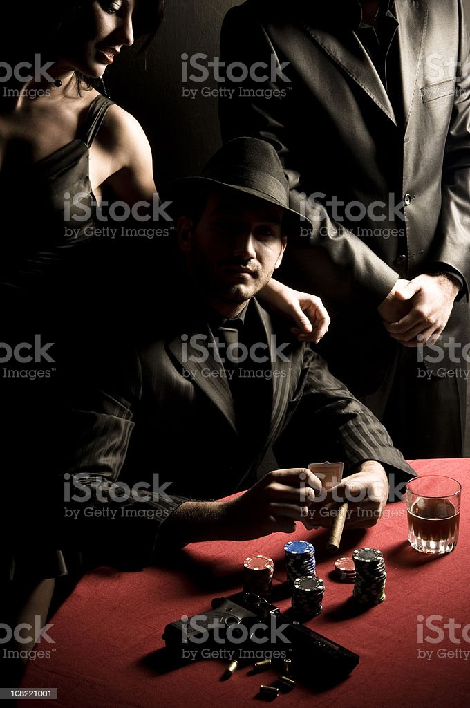 Gangster Man Playing Poker with Gun on Table stock photo