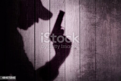 Gangster or investigator or spy silhouette on natural wooden wall. You can see more silhouettes and shadows on my page.