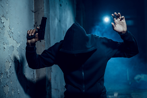 Gangster wearing hooded shirt with a gun