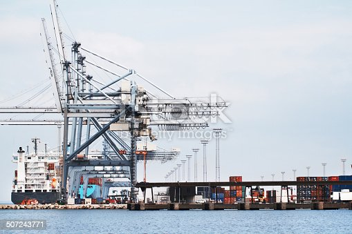 A photo of a harbor with anchored ships, gantry cranes and containers.